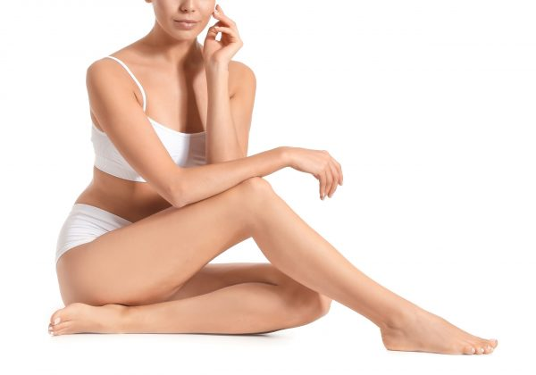 Woman with beautiful legs after depilation on white background